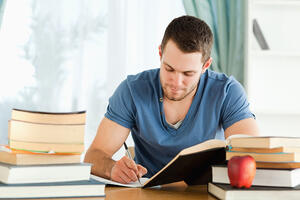 Male student working through his books-1